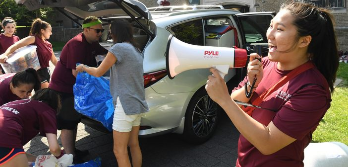 A student volunteer welcomes first year students to the Rose Hill campus through a bullhorn.