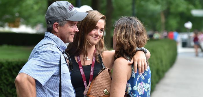 A first year-student and her parents embrace and exchange meaningful glances as they say goodbye.