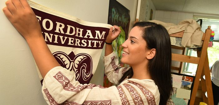 Olivia Jones, a first year student at Fordham College at Rose Hill, hangs a Fordham banner in her room at Alumni Court South