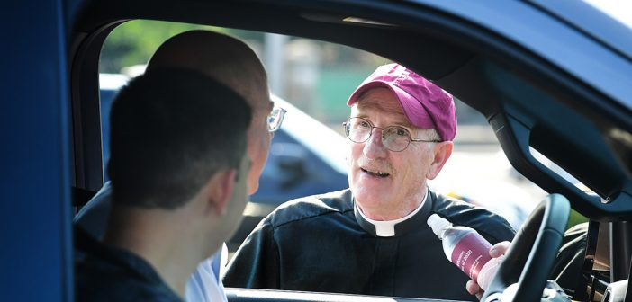 Joseph M. McShane, President of Fordham, greets a family through the driver side of a car arriving at the Rose Hill campus.