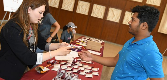 A commuter student receives his name tag at the registration table in the McGinley Center.