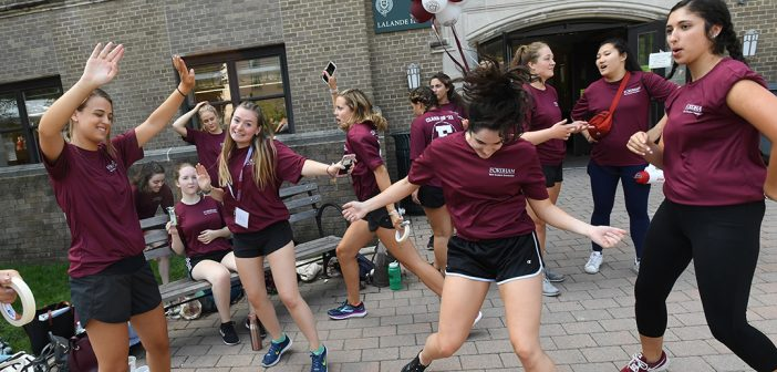 Student volunteers dance in front of the entrance of Martyr's Court on the Rose Hill campus.