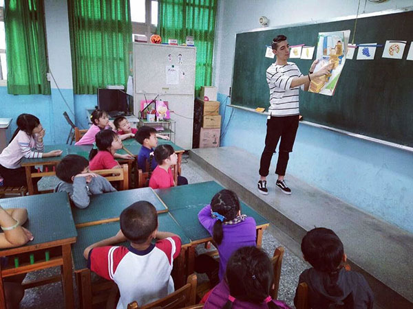 Fordham graduate Erik Angamarca teaches young children in a classroom in Taiwan.