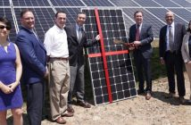 Executives stand in front of a solar panel