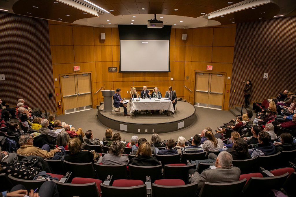 Panelists sit on stage at the McNally Ampitheatre
