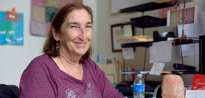 Marilyn Bisberg smiles at the camera in her office.