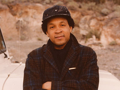 The artists Frederick J Brown in the '70s in plaid wool coat leaning against a car