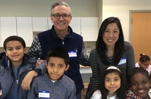 Jennie Park-Taylor standing with Jeffrey Bunzel, a board member at the Hunts Point Alliance for Children, and a few elementary school students at a career mentoring event.