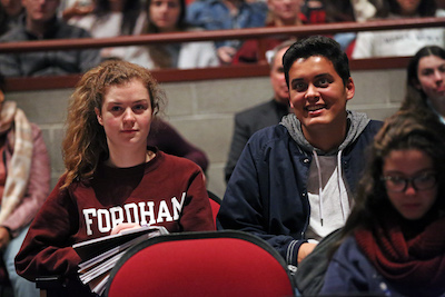 Two students, one in Fordham sweatshirt, sitting together in audience