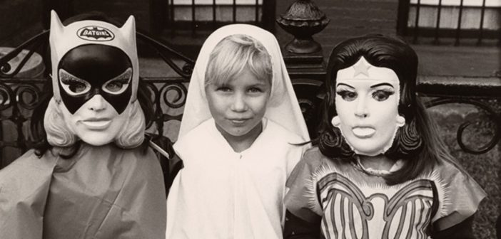 Three girls dressed up as Batgirl, St. Ann, and Wonder Woman for Halloween in 1970s Brooklyn