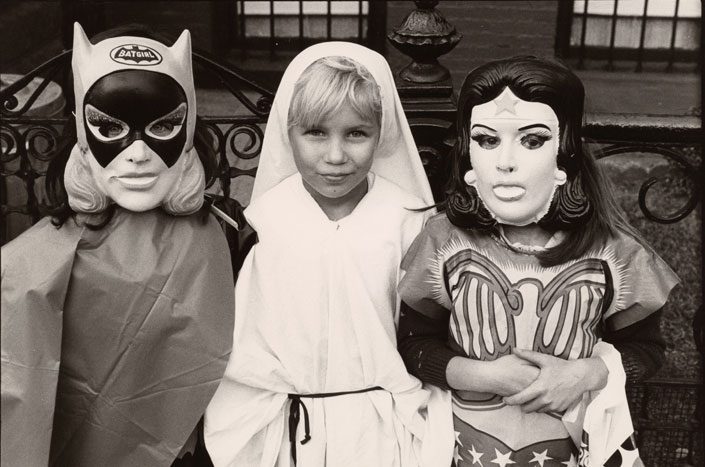 Three kids dressed for Halloween as Batgirl, St. Ann, and Wonder Woman