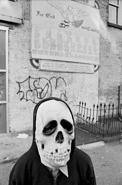 A young boy wears a skull mask for Halloween and stands in front of a World War II memorial