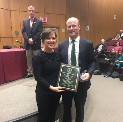 Shannon Hirrel accepts plaque from Sean Lane of the St. Patrick's Day Foundation