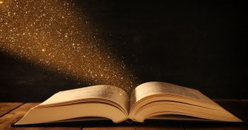 an open book with sparkly dust coming out of it