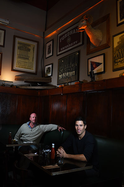 Maxwell's Tribeca Co-Owners Mike Casey, FCRH '96, and Alex Tortolani, FCRH '02, sit under some of the restaurant's Fordham memorabilia.