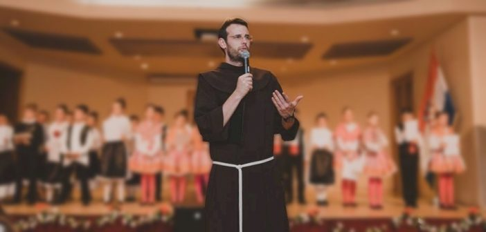 Zeljko Barbaric stands and speaks into a microphone, wearing a Franciscan brown habit.