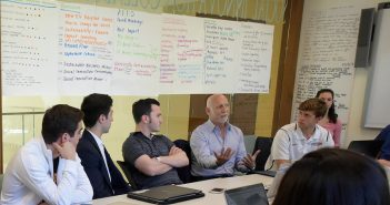 Brent Martini chats with students sitting at a table in the office of the Social Innovation Collaboratory, in Hughes Hall.