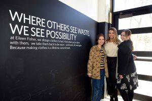 Three female students affiliated with the Social Innovation Collaboratory stand next to a black wall at the Eileen Fisher Company