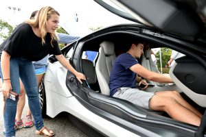 Two Gabelli School of Business students inspect a BMW electric vehicale on the Rose Hill campus.