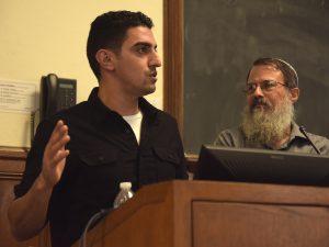 Shadi Abu Awwad speaks from the podium, with Schlesinger beside him