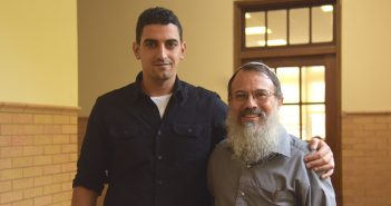 Shadi Abu Awwad and Hanan Schlesinger smile for the camera, with Shadi's arm around Rabbi Schlesinger's shoulder.