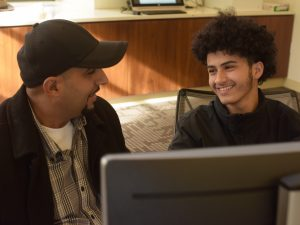 A son smiles at his father behind a computer screen.