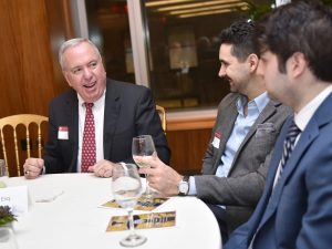 John J. Reddy Jr., Esq., FCRH '76, PAR, speaks with two young men at a table.