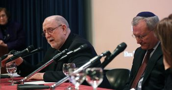 Father Ryan speaks into the mic beside two respondents at the 2018 fall McGinley lecture