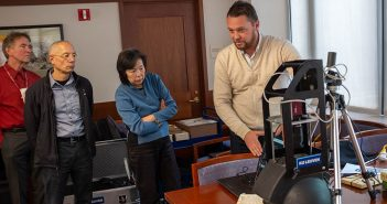 A man demonstrates a scanner to three members of the Fordham Libraries staff