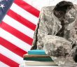 A camouflage military uniform draped over a chair with books