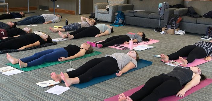 Students lay on yoga mats and towels with their eyes closed and mediate.