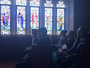 Students sit in pews in the Blue Chapel at the Rose Hill campus, with their eyes closed and their palms facing up; behind them are stained glass windows.