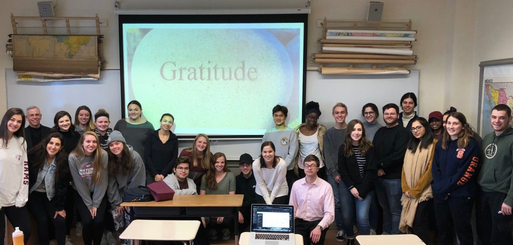 "Father Marcotte's class poses for a group picture at the front of the classroom. They are standing below a projector screen that has a picture of a stone with the engraved word ""Gratitude."""
