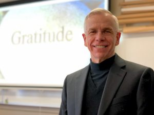 "Father Marcotte smiles next to an image that says the word ""Gratitude."""