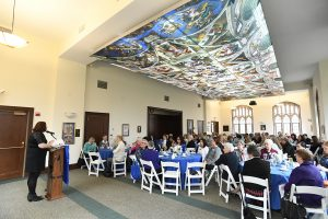 Marymount alumnae sit around tables in Butler Commons, under the reproduction of Michaelangelo's Sistine Chapel paining.