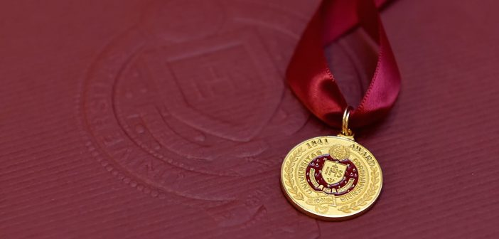 A close-up of the gold medal given to awardees, against a maroon background.