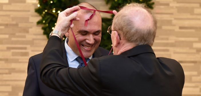 An awardee smiles and looks down as Father McShane slings a medal around his neck.