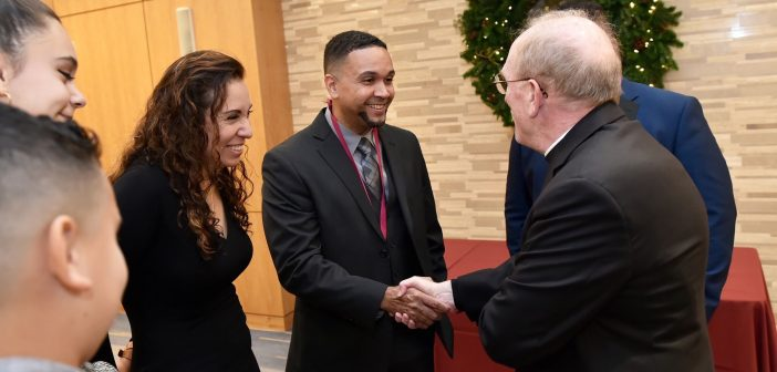 Father McShane shakes hands with an awardee, who is surrounded by his family.