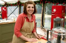 Tina Zaccardi, wearing a beige apron and a dark pink top, smiles for the camera in a kitchen.