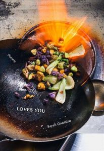 "Front cover of ""Loves You."" Features a pan filled with food and flames."