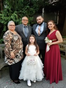 Martinez standing with her husband, son, daughter, and granddaughter at a 2018 wedding.