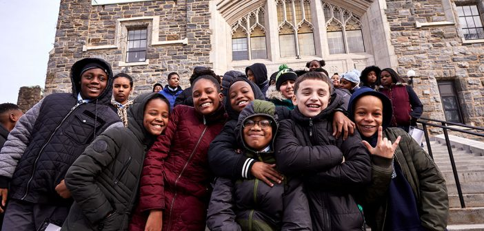 Young Catholic school students in winter coats posing on the Rose Hill campus