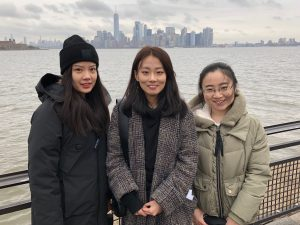 Three students stand in front of the Manhattan skyline.