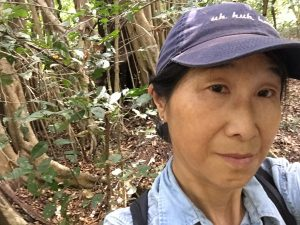 Reiko Matsuda Goodwin poses for a selfie in the forest.