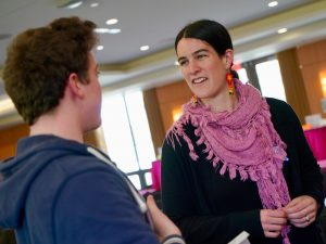 A woman wearing a pink scarf speaks with a male student.