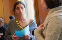 A girl holding a blue sheet of paper listens intently to another student.