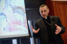 Bishop Caggiano gestures with his hands in front of a PowerPoint slide.