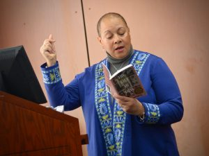 """Maria Aponte stands in front of a podium and reads a poem from her second book, """"The Gift of Loss."""""""