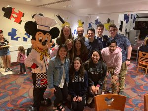 Gabelli students pose for a picture with Mickey Mouse