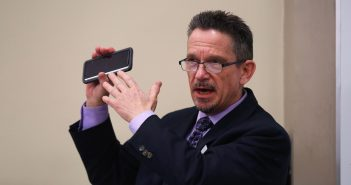 Kirk Bingaman holds up his black smartphone at the podium.